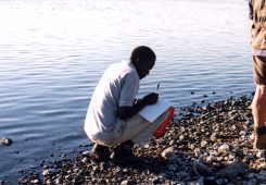 Kibai (Joshua0 Chebotibin, a university student, records data at waters' edge.